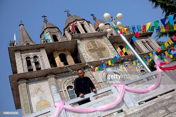 Chinese rural Catholic stands outside a church at Paowo village on May 3 2013 in Baoji China The Shizishan Mountain located in Paowo village...