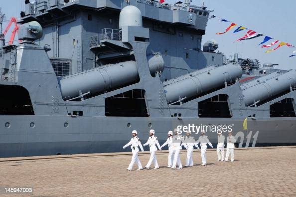 Chinese sailors march pass the Russian destroyer Admiral Vinogradov berthed at the People's Liberation Army naval base in Qingdao northeastern...