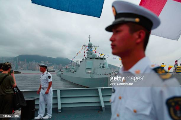 Chinese sailors on board the Yinchuan a People's Liberation Army Navy Type 052D destroyer keep watch on visitors as the PLA Navy's Type 052C...