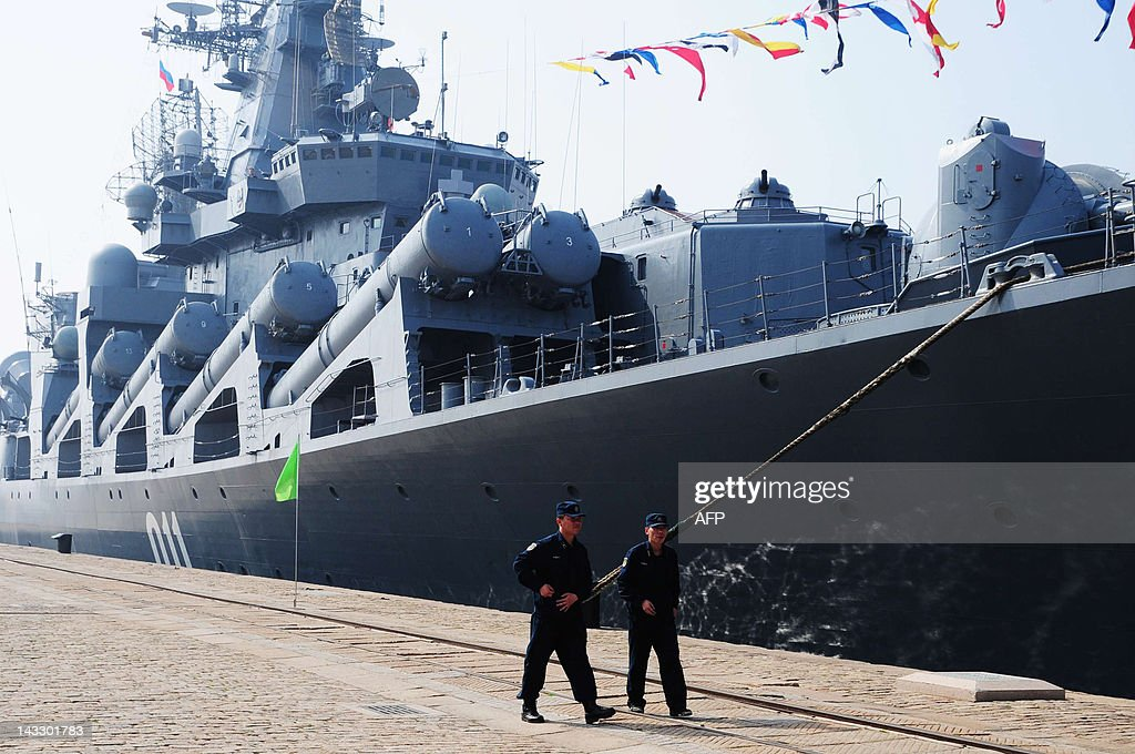 Chinese sailors walk by the Russian destroyer Admiral Vinogradov berth at the People's Liberation Army (PLA) naval base in Qingdao, northeastern China's Shandong province on April 23, 2012, prior to the start of the Sino-Russian joint naval exercises. China and Russia launched their first joint naval exercises, with war games in the Yellow Sea that come amid tensions between China and its Asian neighbours over territorial claims. CHINA
