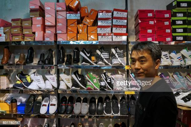 A Chinese salesman looks on as he sells copies of various American footwear brands inside a shopping complex in Shanghai on August 15 2017 Trade...