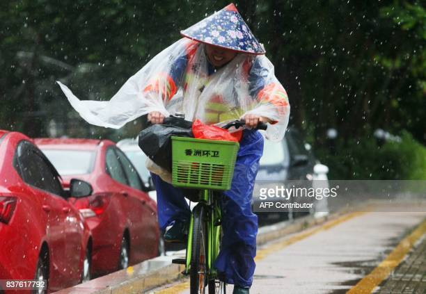 Chinese sanitation worker rides a bicycle against the strong wind caused by Typhoon Hato on a road along the seacoast in Zhuhai in China's southern...