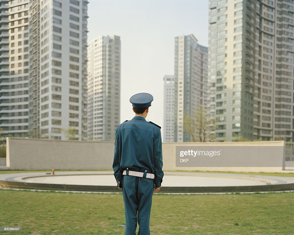 Chinese security guard in front of high rises. : Stock Photo