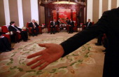 Chinese security guard motions for journalists to leave after a photo call with Cuban President Raul Castro during a meeting held at the Zhongnanhai...