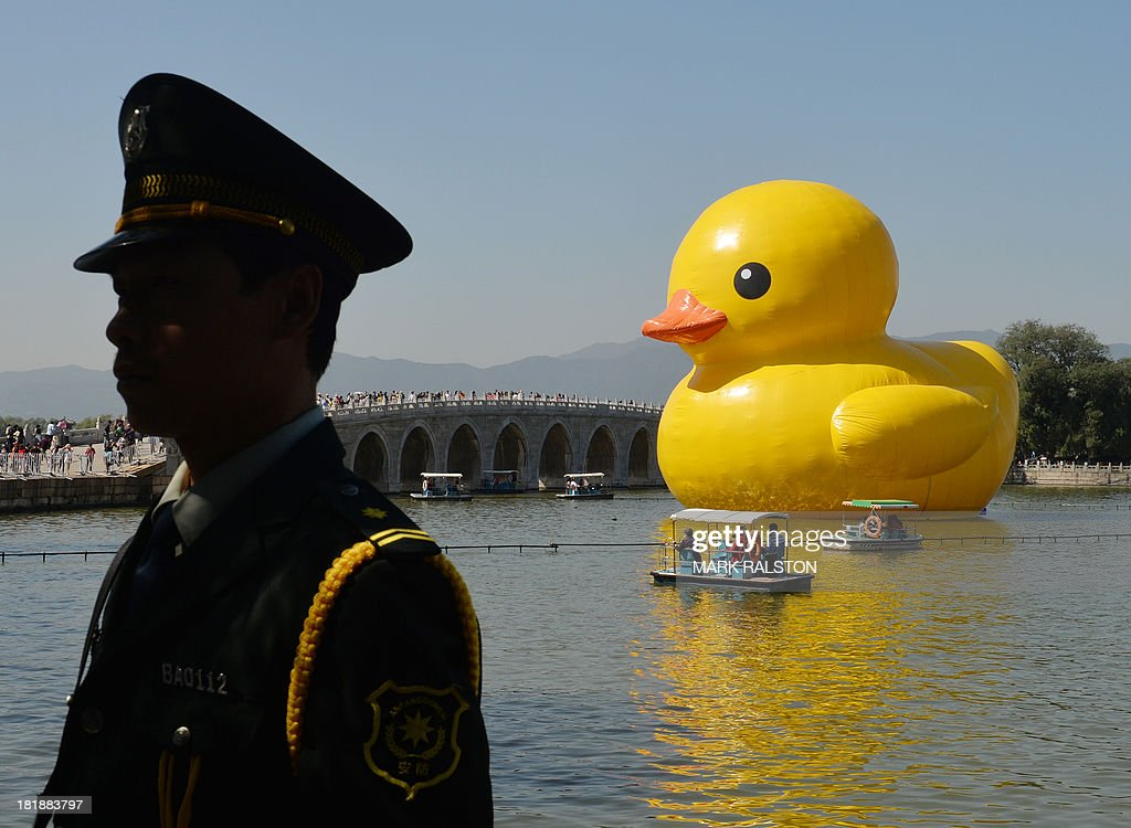 A Chinese security guard (L) stands on a bank as visitors look at an 18-metre tall inflatable duck after its move to Lake Kunming at the historic Summer Palace in Beijing on September 26, 2013. The duck designed by Dutch artist Florentijn Hofman is to be displayed at Beijing's Garden Expo Park and the Summer Palace, from September to October as part of a world tour of 13 cities across 10 countries. AFP PHOTO / Mark RALSTON