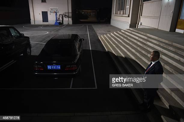 A Chinese security official watches over cars parked on a basketball court in the Zhongnanhai leadership compound while US President Barack Obama has...