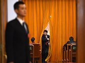 Chinese security personnel stand guard as a delegate makes his way out during the opening of the 3rd Session of the 12th National People's Congress...