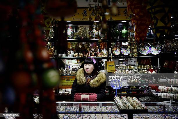 Chinese shopkeeper waits for customers at a market on January 19 2016 in Beijing China In 2015 China's economy grew at its slowest rate in a quarter...