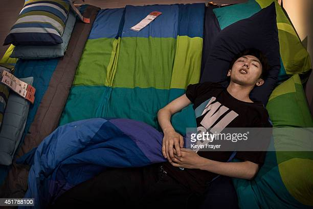 Chinese shopper sleeps on a bed in the showroom of the IKEA store on July 6 2014 in Beijing China Of the world's ten biggest Ikea stores 8 of them...