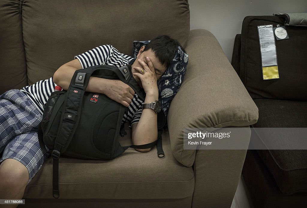 A Chinese shopper sleeps on a sofa in the showroom of the IKEA store on July 6, 2014 in Beijing, China. Of the world's ten biggest Ikea stores, 8 of them are in China to cater to the country's growing middle class. The stores are designed with extra room displays given the tendency for customers to make a visit an all-day affair. Store management does not discourage shoppers from sleeping on Ikea furniture, even marking them with signs inviting customers to try them out.