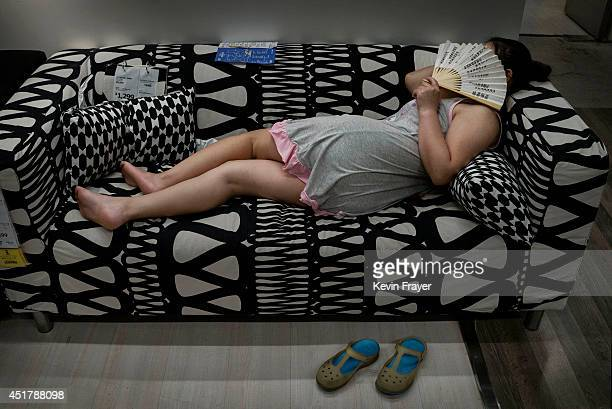 Chinese shopper sleeps on a sofa in the showroom of the IKEA store on July 6 2014 in Beijing China Of the world's ten biggest Ikea stores 8 of them...