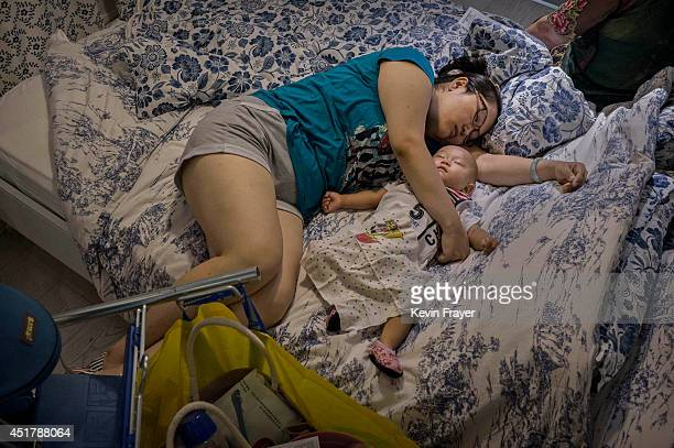 Chinese shopper sleeps with her child on a bed in the showroom of the IKEA store on July 6 2014 in Beijing China Of the world's ten biggest Ikea...