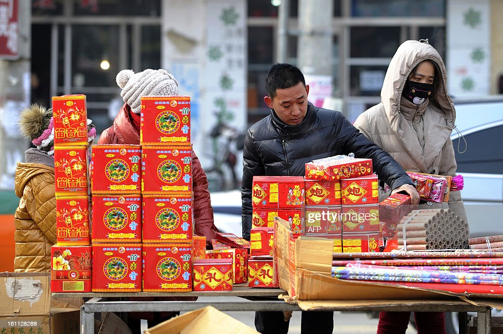 Chinese shoppers browse through fireworks for the celebration of the Chinese New Year in Fuxin, in the northeast Liaoning province on February 9, 2013, a day before the Lunar New Year. China is preparing to welcome the Lunar New Year of the Snake which falls on Febraury 10. AFP PHOTO / WANG ZHAO