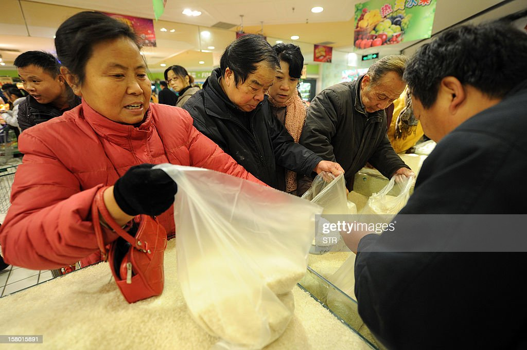 Chinese shoppers buy rice at a supermarket in Hefei, east China's Anhui province on December 9, 2012. China's inflation rate accelerated slightly to 2.0 percent in November, the National Bureau of Statistics said on December 9. CHINA
