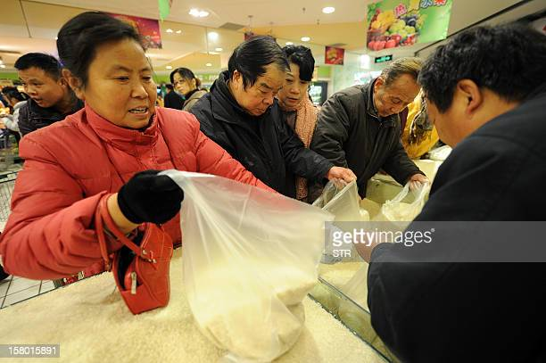 Chinese shoppers buy rice at a supermarket in Hefei east China's Anhui province on December 9 2012 China's inflation rate accelerated slightly to 20...