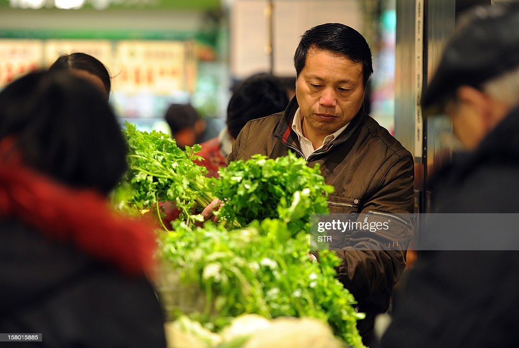 Chinese shoppers buy vegetables at a supermarket in Hefei, east China's Anhui province on December 9, 2012. China's inflation rate accelerated slightly to 2.0 percent in November, the National Bureau of Statistics said on December 9. CHINA OUT AFP PHOTO