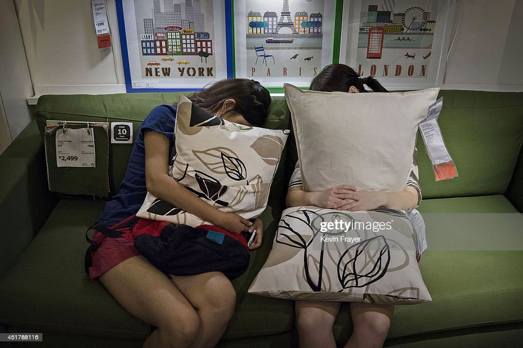 Chinese shoppers clutch pillows as they sleep on a sofa in the showroom of the IKEA store on July 6, 2014 in Beijing, China. Of the world's ten biggest Ikea stores, 8 of them are in China to cater to the country's growing middle class. The stores are designed with extra room displays given the tendency for customers to make a visit an all-day affair. Store management does not discourage shoppers from sleeping on Ikea furniture, even marking them with signs inviting customers to try them out.