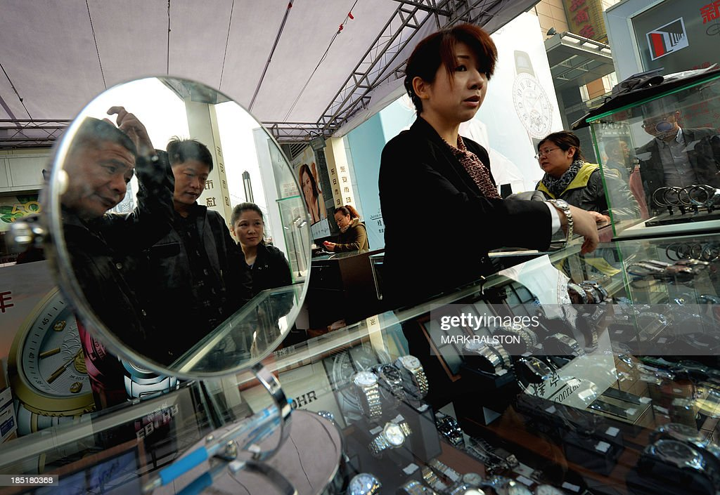 Chinese shoppers look at watches for sale on the Wangfujing shopping street in Beijing on October 18, 2013. China's economy expanded 7.8 percent year-on-year in July-September, data showed, snapping two quarters of slowing growth, but analysts questioned whether the improvement was sustainable. The gross domestic product (GDP) figure for the world's second-largest economy, a key driver of global growth, matched the median forecast in a survey of 11 analysts by AFP. AFP PHOTO/Mark RALSTON