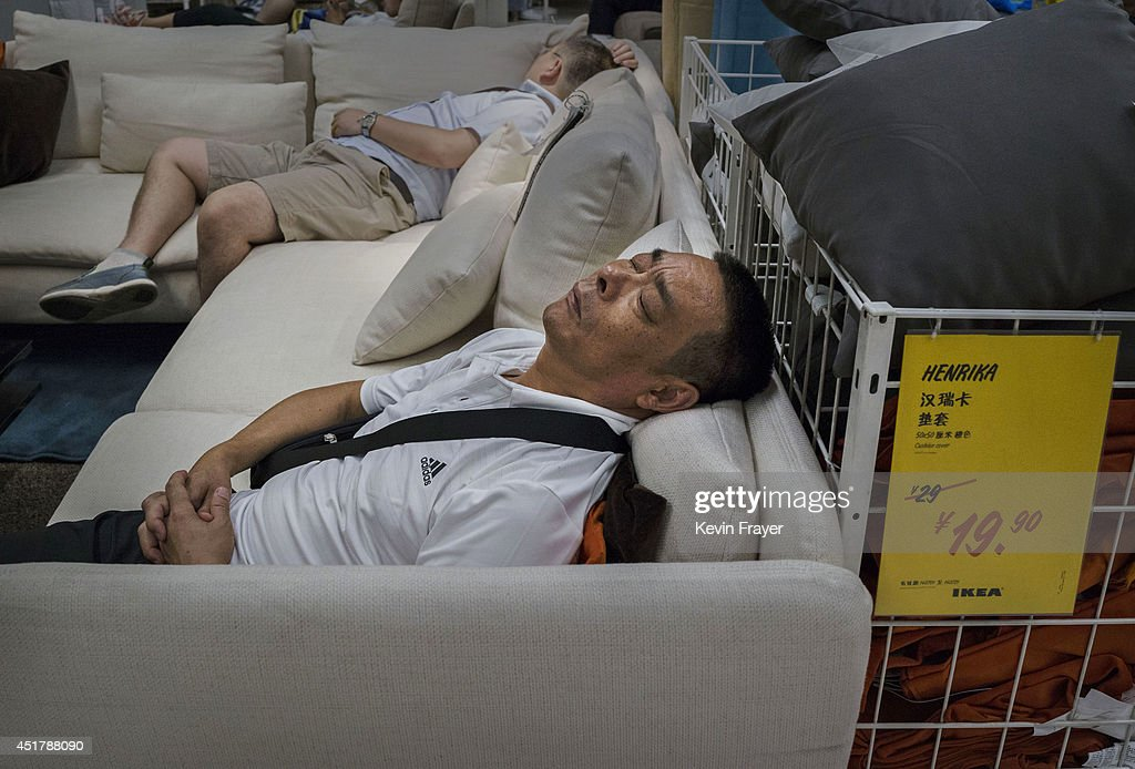 Chinese shoppers sleep on a sofa in the showroom of the IKEA store on July 6, 2014 in Beijing, China. Of the world's ten biggest Ikea stores, 8 of them are in China to cater to the country's growing middle class. The stores are designed with extra room displays given the tendency for customers to make a visit an all-day affair. Store management does not discourage shoppers from sleeping on Ikea furniture, even marking them with signs inviting customers to try them out.