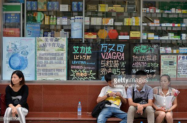 Chinese shoppers wait outside pharmacy selling medicine in Beijing on August 13 2013 Beijing city health and corruption officials have launched an...