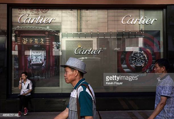Chinese shoppers walk passed a luxury store in an upscale shopping district on August 28 2015 in Beijing China China's government is relying on...