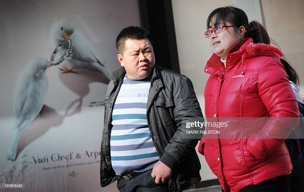Chinese shoppers walk past a jewellery store in the Wangfujing shopping street at the start of the 'Year of the Dragon' in Beijing on January 29 2012...