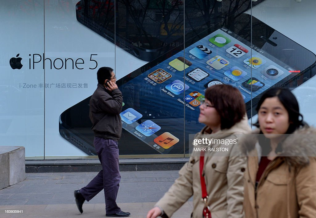 Chinese shoppers walk past an advertisement for an IPhone outside an Apple reseller in Beijing on March 18, 2013. Apple was recently targeted over its consumer-service practices in China during a state television broadcast focusing on consumer rights, allegedly claiming the US company treated its Chinese customers differently than in other countries when it came to product service and warranties. A storm or criticism, both pro and against, swamped social media websites in the aftermath of the broadcast. China is the second-biggest market for Apple after the United States.