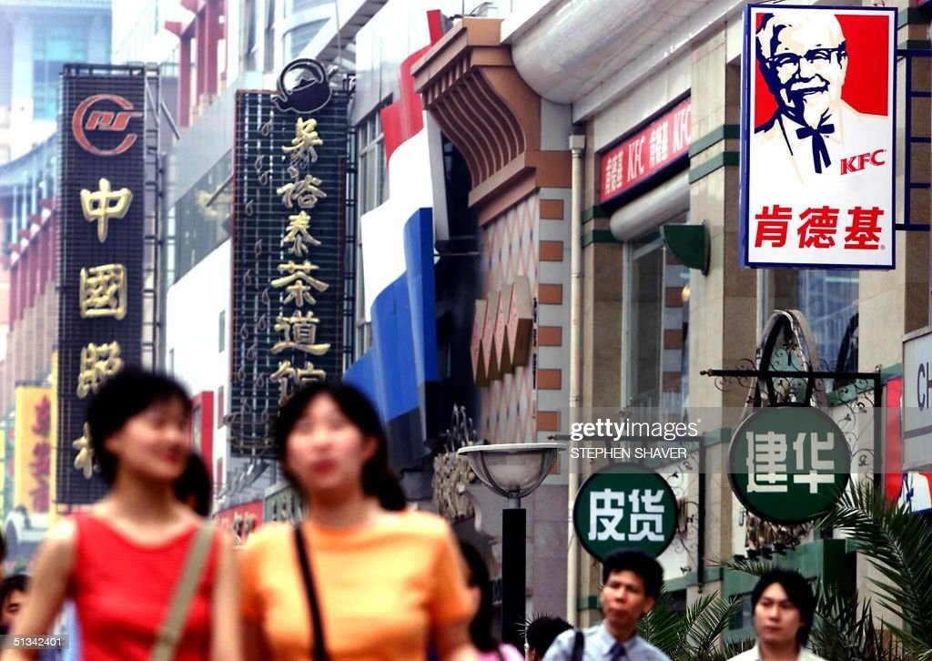 Chinese shoppers walk through Beijing's main downtown shopping promenade past a Kentucky Fried Chicken franchise 11 June 2001 KFC is one of the most...