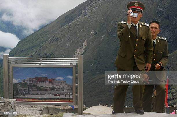 Chinese soldier takes a picture as he approaches the border fence at Nathu La Trade between India and China is set to begin on July 6th 2006 as the...