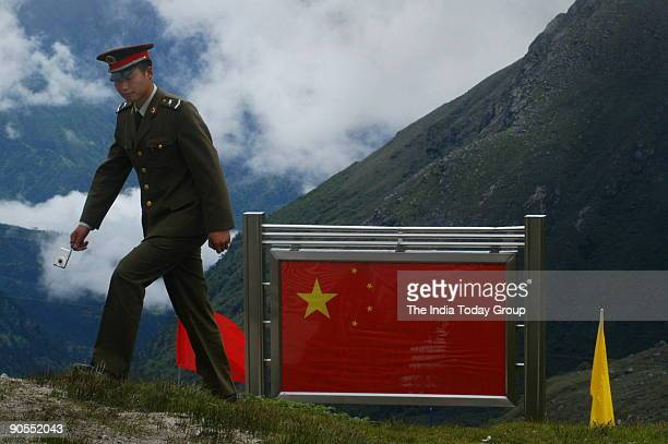 Chinese soldier walks near the border fence at Nathu LaTrade between India and China is set to begin on July 6th 2006 as the 14000ft high Nathu La...