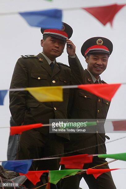 Chinese soldiers are seen through flags put up to celebrate the opening of the Nathu La PassTrade between India and China is set to begin on July 6th...