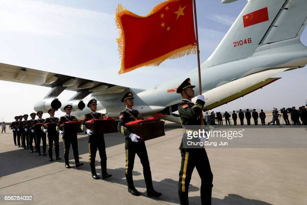 Chinese soldiers carry caskets containing the remains of Chinese soldiers with a Chinese national flag during the handing over ceremony at the...