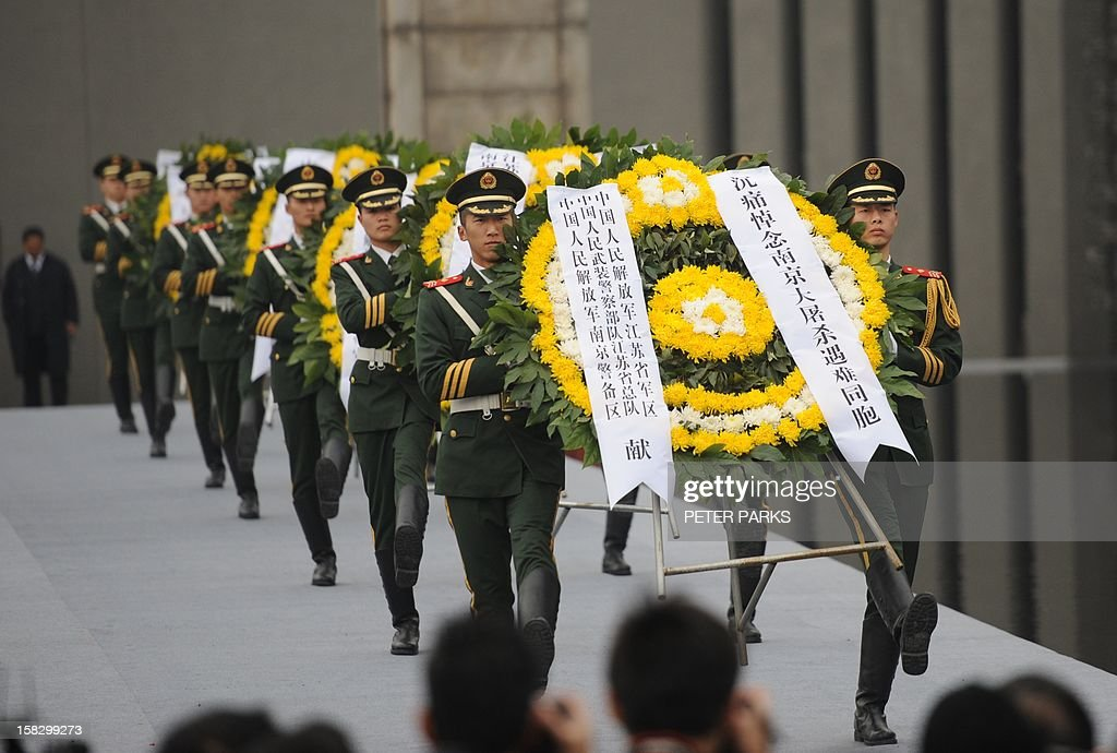 Chinese soldiers carry wreaths at a ceremony for victims to mark the 75th anniversary of the Nanjing massacre at the Memorial Museum in Nanjing on December 13, 2012. Air raid sirens sounded in the Chinese city of Nanjing on December 13 as it marked the 75th anniversary of the mass killing and rape committed there by Japanese soldiers -- with the Asian powers' ties at a deep low. AFP PHOTO/Peter PARKS