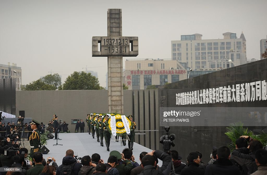 Chinese soldiers (C) carry wreaths at a ceremony for victims to mark the 75th anniversary of the Nanjing massacre at the Memorial Museum in Nanjing on December 13, 2012. Air raid sirens sounded in the Chinese city of Nanjing on December 13 as it marked the 75th anniversary of the mass killing and rape committed there by Japanese soldiers -- with the Asian powers' ties at a deep low. AFP PHOTO/Peter PARKS