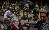 Chinese soldiers in riot gear secure the area outside the Id Kah Mosque after Imam Jumwe Tahir was killed by assailants following early morning...
