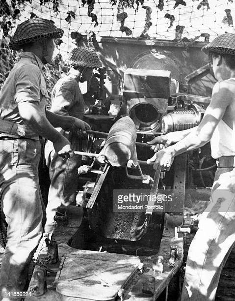 Chinese soldiers loading a 155 mm gun a in a camouflaged position Bhamo January 1945