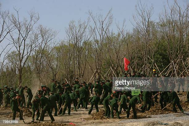 Chinese soldiers plant trees during a tree planting activity for the 2008 Olympic Games at the Olympic Park on April 21 2007 in Beijing China China...