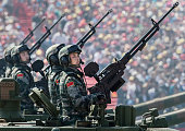 Chinese soldiers ride in an armoured vehicle as they hold machine guns while passing in front of Tiananmen Square and the Forbidden City during a...