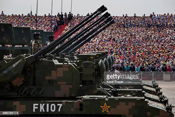 Chinese soldiers ride in armoured vehicles as they drive in front of Tiananmen Square and the Forbidden City during a military parade on September 3...