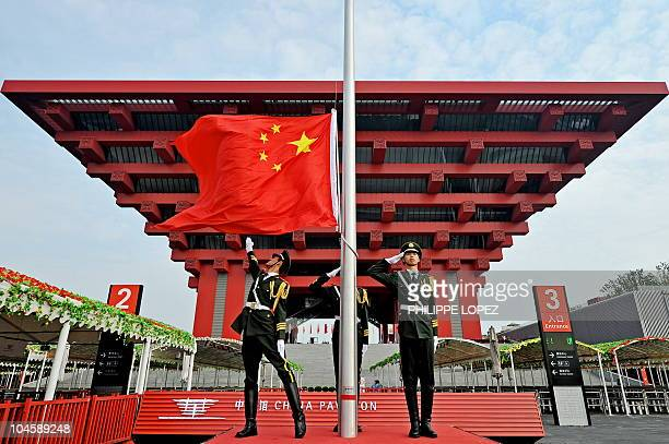Chinese soldiers unwrap the national flag in front of the Chinese pavilion at the World Expo 2010 on October 1 2010 for the China national pavilion...
