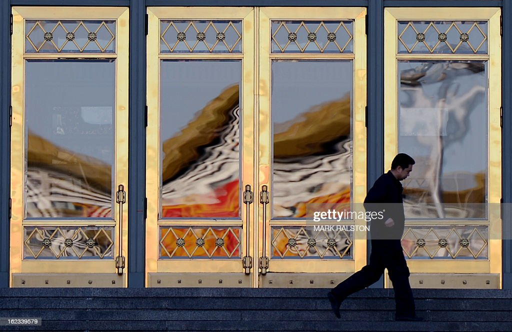 A Chinese staff member passes by the doors of China's parliament building known locally as 'The Great Hall of the People' as the city prepares for news weeks legislature meetings, in Beijing on February 22, 2013. China has fixed March 5, 2013, as the date it will convene a key legislative session, state media reported Friday, with new Communist Party chief Xi Jingping set to become president during the two-week meeting. The announcement comes after the Communist Party in November chose current Vice President Xi to take over the reins of the ruling party from current President Hu Jintao. AFP PHOTO/Mark RALSTON
