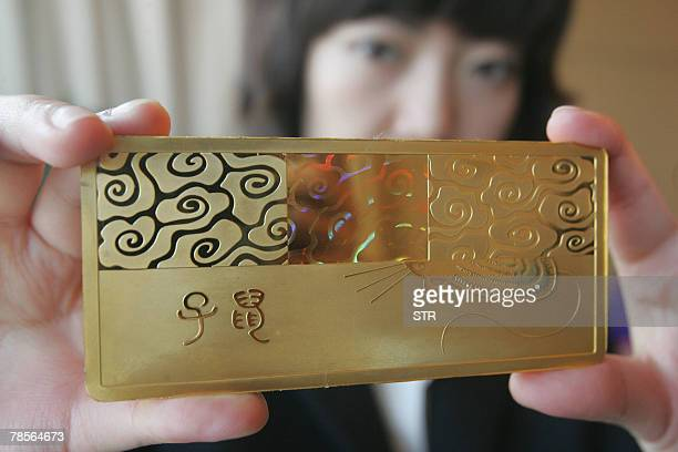 A Chinese staff shows off a gold bullion with a design of the rat in Beijing 17 December 2007 The ornament will go on sale on 22 December to mark the...