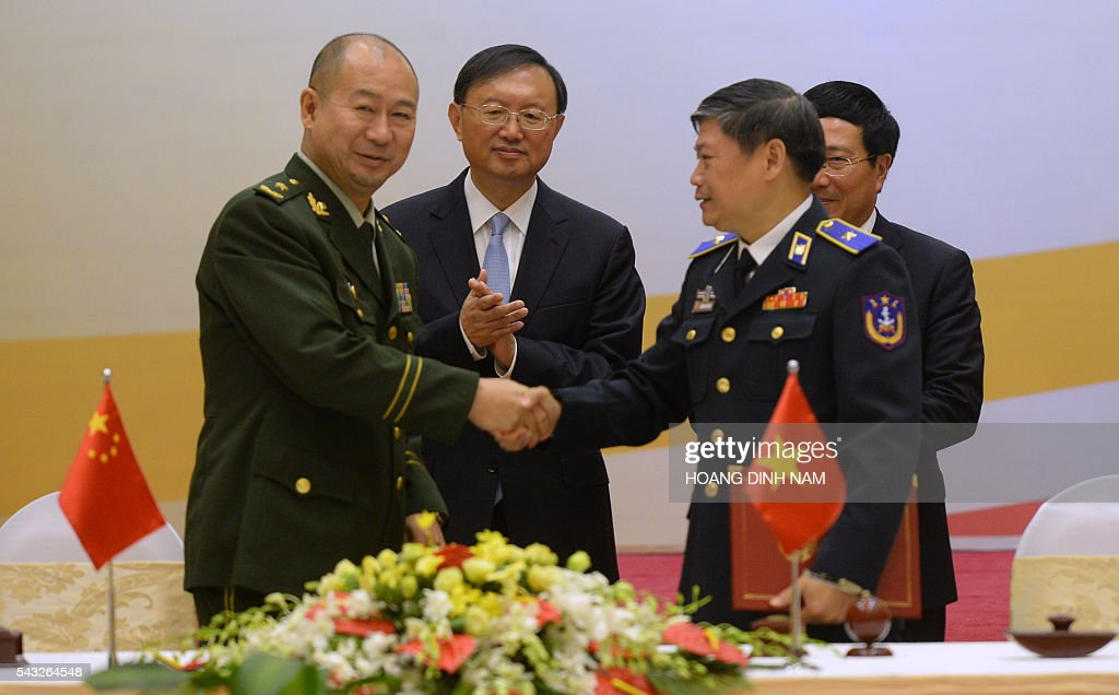 Chinese State Councillor Yang Jiechi (2nd L) and Vietnamese Deputy Prime Minister and Minister of Foreign Affairs Pham Binh Minh (R) applaud after they witnessed the signing of bilateral agreements in Hanoi on June 27, 2016. Yang is in Vietnam to attend the 9th joint-meeting on bilateral cooperation between Vietnam and China. / AFP / HOANG