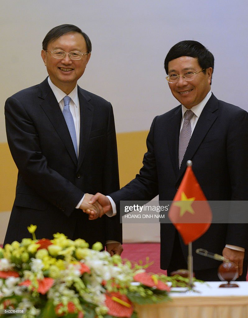 Chinese State Councillor Yang Jiechi (L) shakes hands with Vietnamese Deputy Prime Minister and Minister of Foreign Affairs Pham Binh Minh (R) after they witnessed the signing of bilateral agreements in Hanoi on June 27, 2016. Yang is in Vietnam to attend the 9th joint-meeting on bilateral cooperation between Vietnam and China. / AFP / HOANG