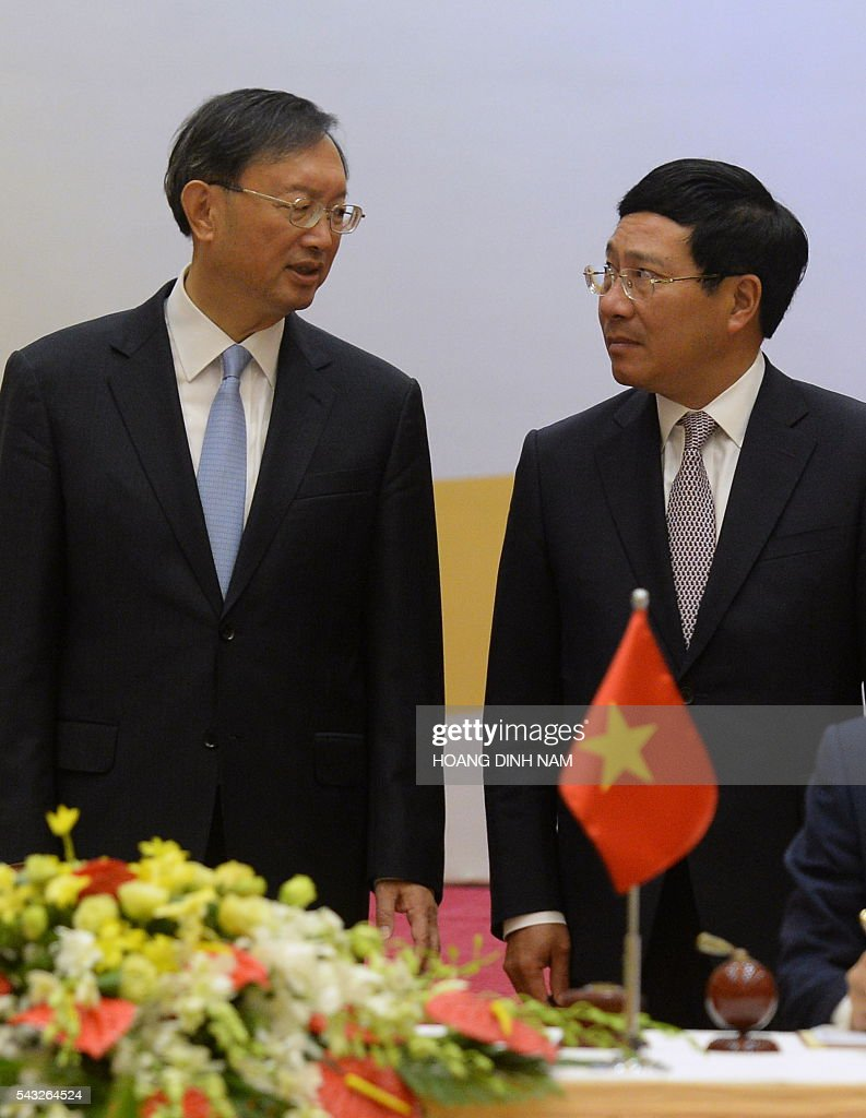 Chinese State Councillor Yang Jiechi (L) speaks with Vietnamese Deputy Prime Minister and Minister of Foreign Affairs Pham Binh Minh as they witness the signing of bilateral agreements in Hanoi on June 27, 2016. Yang is in Vietnam to attend the 9th joint-meeting on bilateral cooperation between Vietnam and China. / AFP / HOANG