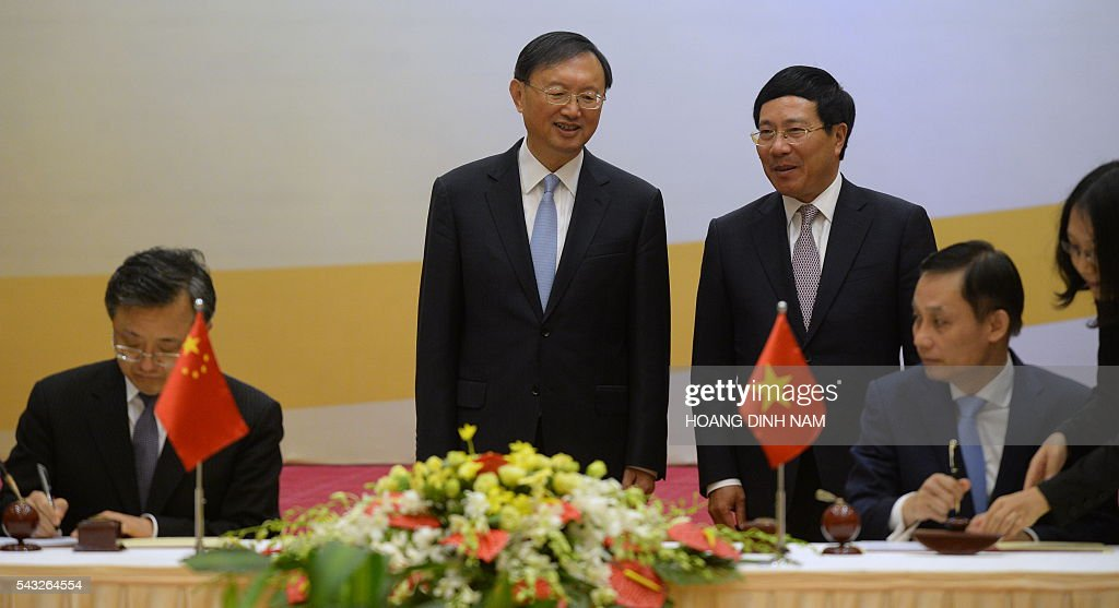 Chinese State Councillor Yang Jiechi (centre L) speaks with Vietnamese Deputy Prime Minister and Minister of Foreign Affairs Pham Binh Minh (centre R) as they witness the signing of bilateral agreements in Hanoi on June 27, 2016. Yang is in Vietnam to attend the 9th joint-meeting on bilateral cooperation between Vietnam and China. / AFP / HOANG