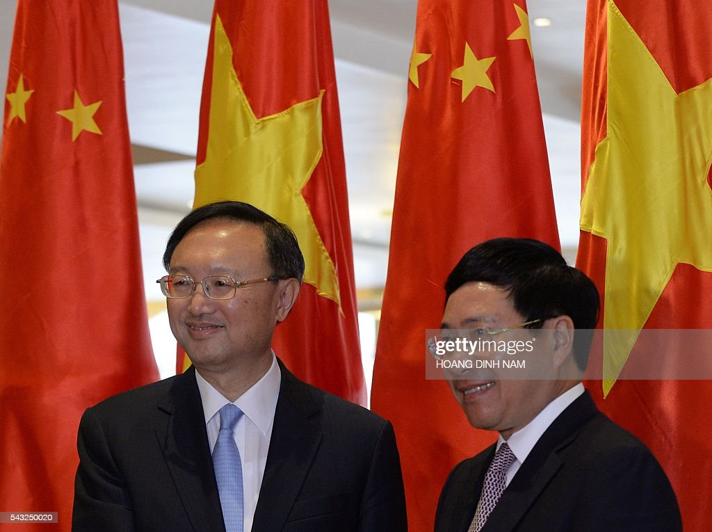 Chinese State Councilor Yang Jiechi (L) shakes hands with Vietnamese Deputy Prime Minister and Minister of Foreign Affairs Pham Binh Minh as they meet in Hanoi on June 27, 2016. Yang is in Vietnam to attend the 9th joint-meeting on bilateral cooperation between Vietnam and China. / AFP / HOANG