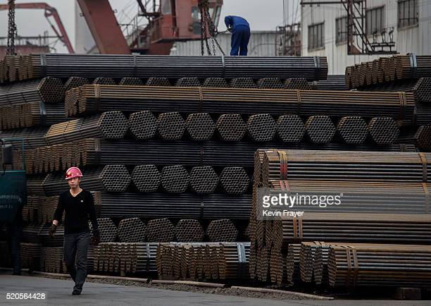 Chinese steel worker walks past steel rods at a plant on April 6 2016 in Tangshan Hebei province China China's government plans to slash steel...