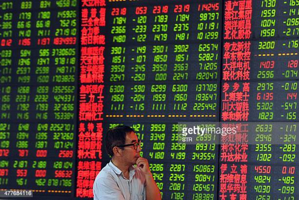 A Chinese stock investor checks share prices at a securities firm in Fuyang in China's Anhui province on June 19 2015 Shanghai shares plunged 642...