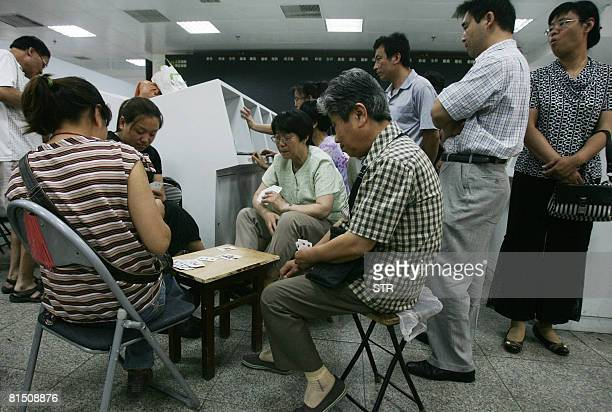 Chinese stock investors play cards at a security firm in Beijing on June 10 2008 Chinese share prices tumbled to close 773 percent down the biggest...